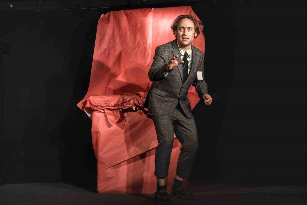 Mit einem riesigen, in rotem Papier eingepackten Geschenk für Lastwagenfahrer Waldemar (Joachim Aßfalg) kommt die Geschichte ins Rollen. In seinem Stück beschäftigt sich der aus Seekirch stammende Schauspieler und Autor damit, was die Digitalisierung mit den Menschen macht. (Foto: Aylin Kaip)
